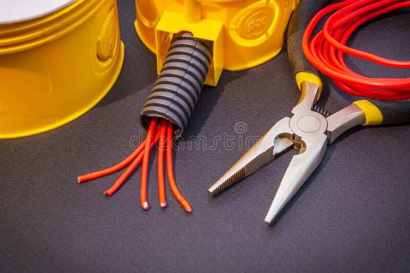 Spare parts, tool and wires for replacement or repair of electrical equipment. On black background royalty free stock photography