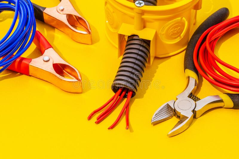 Spare parts, tool and wires for replacement or repair of electrical equipment. On yellow background stock images