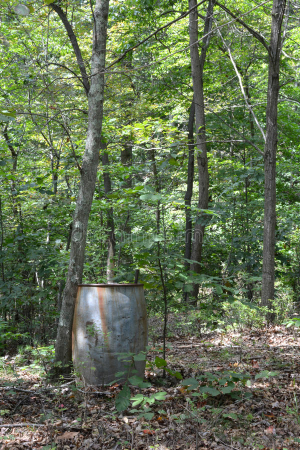 Spare rain barrel. A spare rain barrel in the woods awaits its turn catching water off a roof. Standing in front of the cabin, this barrel is in the edge of the royalty free stock photo