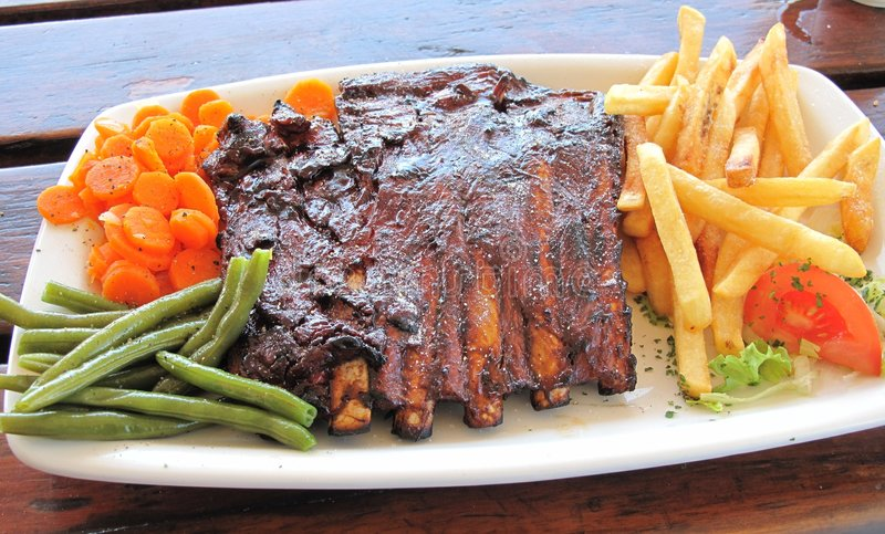 Spare ribs. Main course of spare ribs with green beans, carrots and chips served outside on a sunny day stock images