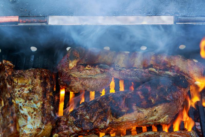 Grilled pork ribs on the flaming grill cooking on barbecue grill for stock photos