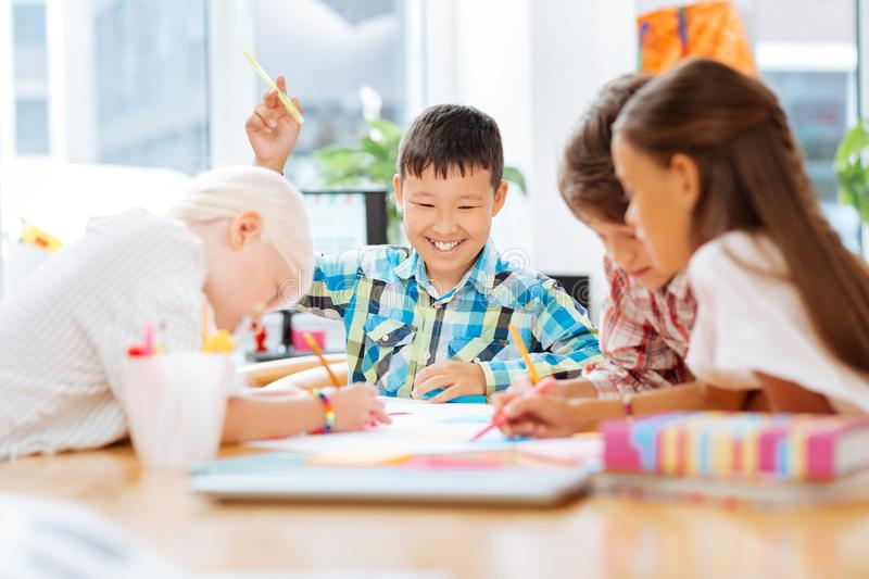 Excited smiling kids drawing together at school royalty free stock photo