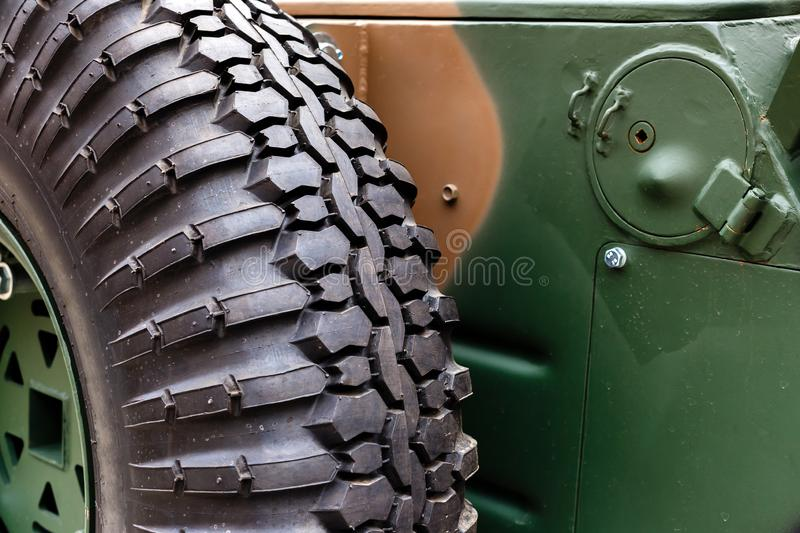 Spare wheel close-up mounted on the body of combat vehicle. Military industry concept stock image