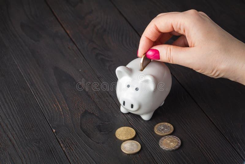 Spareinlagen, Geld, Rentenversicherung, Ruhestand und Leutekonzept - nah oben von der ?lteren Frauenhand, die M?nze in Sparschwei stockbilder