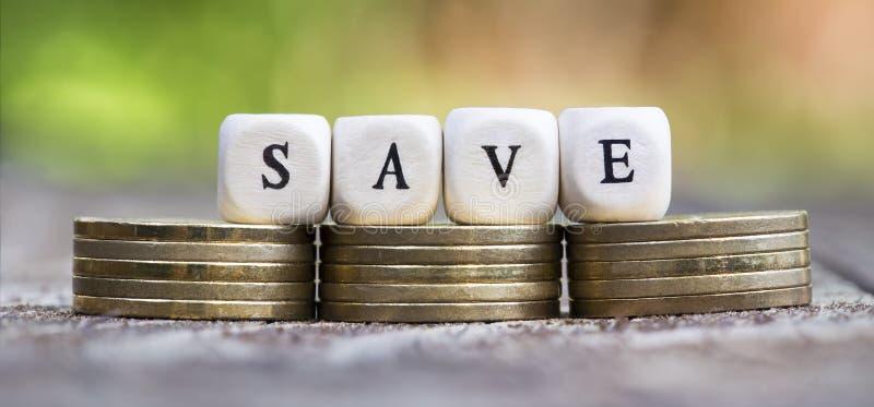 Sparen geld - dobbelt op gouden muntstukken stock afbeeldingen