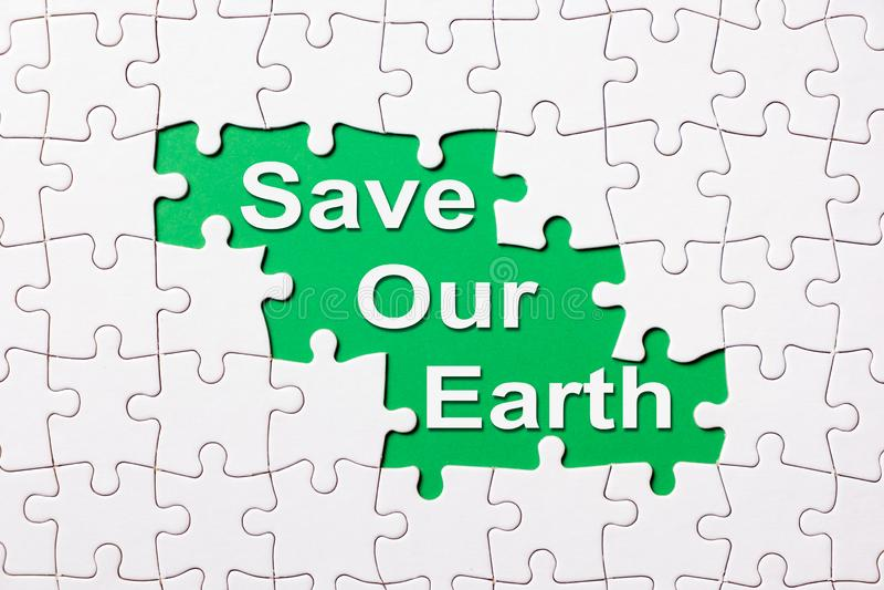 Sparen onze aarde openbaart het woord onder puzzel royalty-vrije stock fotografie