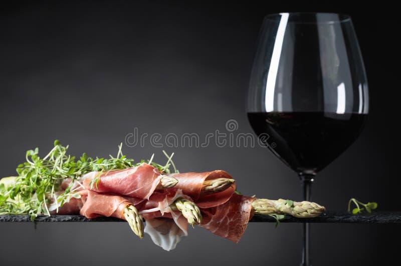 Spargel eingewickelt im Prosciutto mit Rotwein lizenzfreie stockfotografie