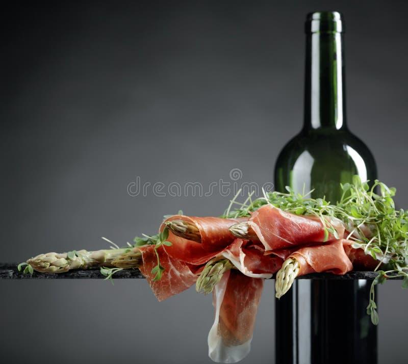 Spargel eingewickelt im Prosciutto mit Rotwein lizenzfreie stockbilder