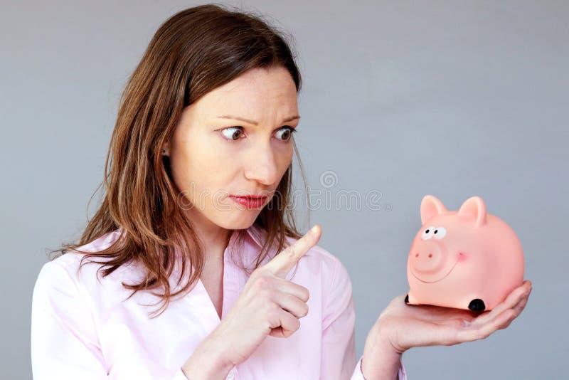 Spargris för rosa färger för moneybox för stressad kvinna för pengarbesparingar hållande royaltyfri foto
