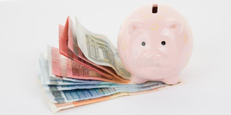 Spargris med euroräkningar på en vit bakgrund arkivbild