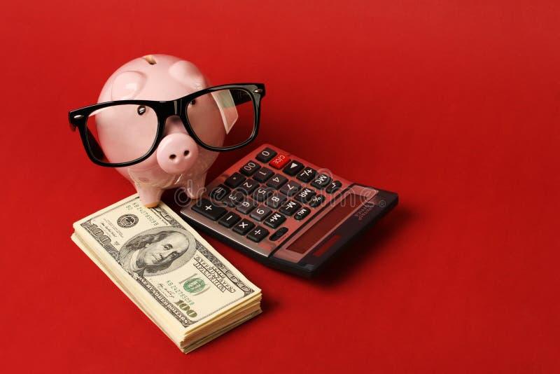 Spargris med exponeringsglas som står på bunt av pengar och räknemaskinen arkivfoton