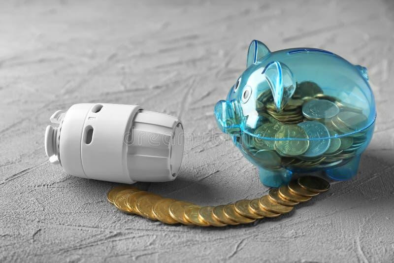 Spargris med mynt och termostat på texturerad bakgrund V?rma sparande begrepp royaltyfri fotografi