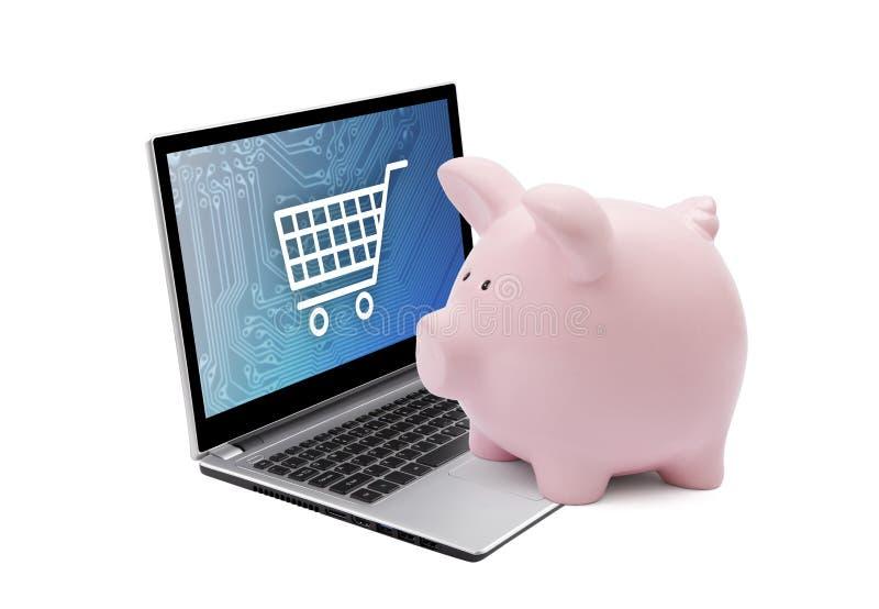 Spargris och bärbar dator med diagrammet för shoppingvagn En handinnehavkrus av pengar stock illustrationer