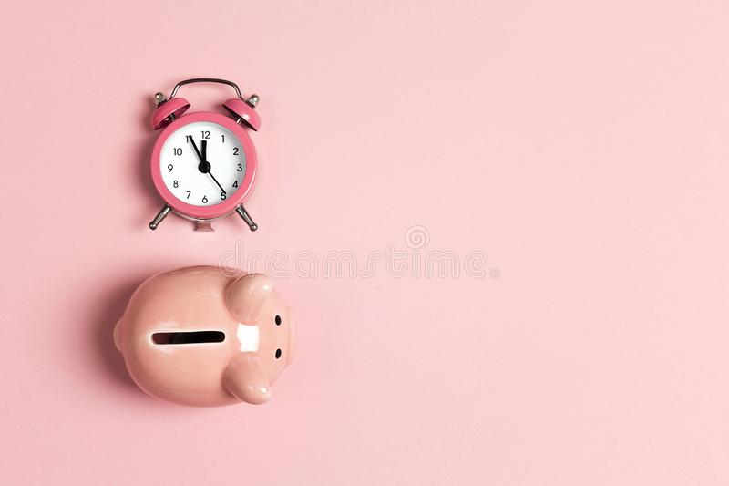 Spargris och klassisk ringklocka på rosa bakgrund Tid till sparande, pengar, bankrörelsebegrepp arkivfoto