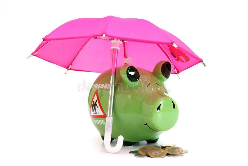 Spargris och mynt under paraplybegrepp av avgångbesparingfonden arkivfoton