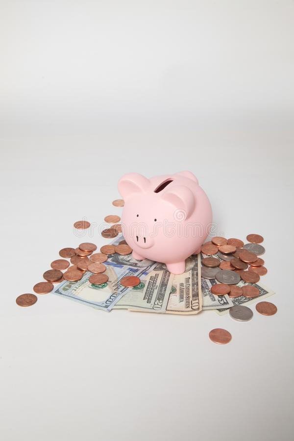 Spargris på högen av räkningar och mynt arkivfoton