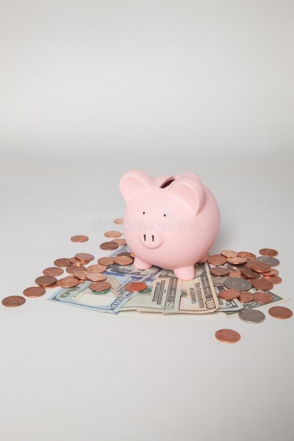 Spargris på högen av räkningar och mynt royaltyfria bilder