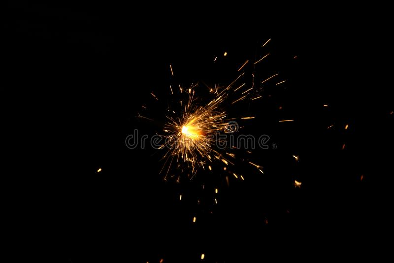 Sparks from metal work in dark room. Spark came from metal work in steel factory. it spread spark all the direction. it appear in cracks while function time. it royalty free stock images