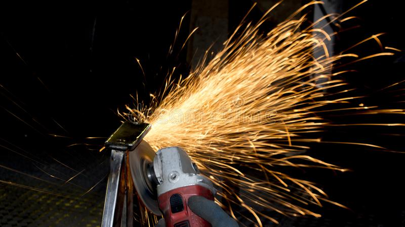Spark on dark background. Processing of metal products and metal structures at the factory, factory, enterprise and organization. stock images