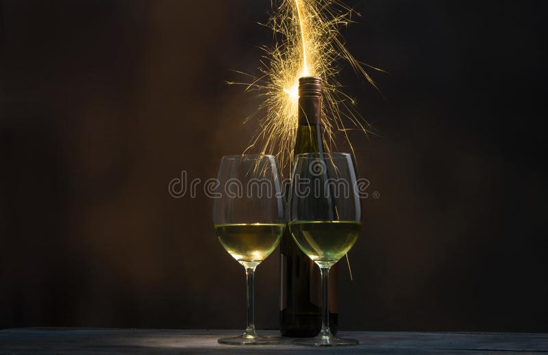 A spark of fireworks became the background for a bottle of wine and two glasses filled with wine. Isolated on celebration and holiday concept stock images