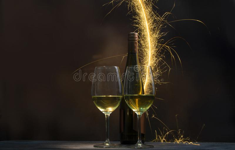A spark of fireworks lit into the background of a bottle of wine and two glasses filled with wine. Isolated on new year and holiday concept royalty free stock photo