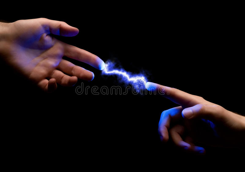 Spark between hands. Blue powerful electric spark between two fingers of mans hands on black background stock photo