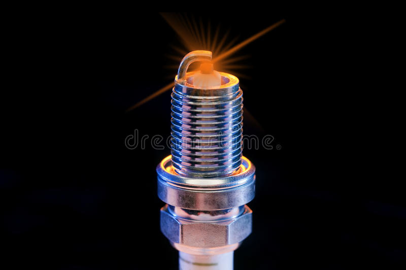 Spark plug. Side lit by blue light on black stock photo