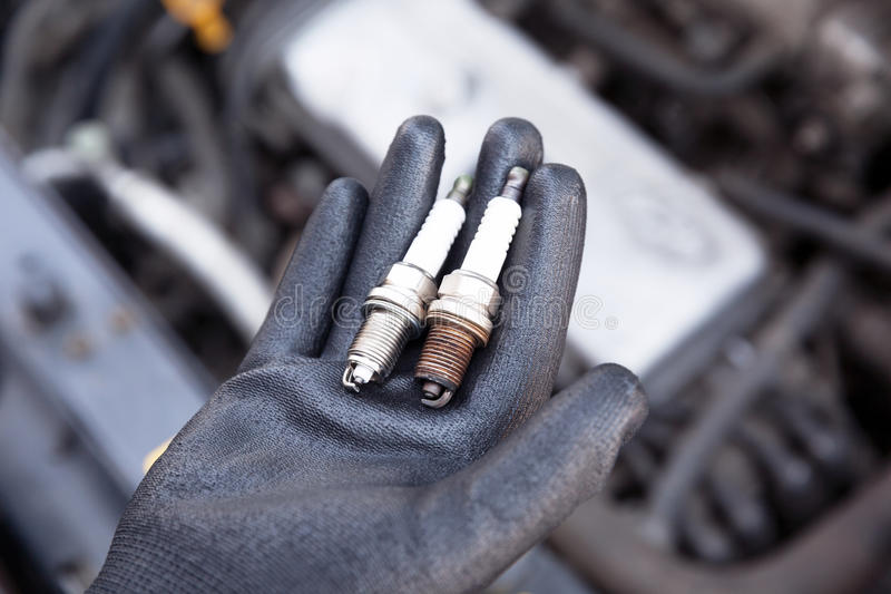 Spark plug, old and new. Auto mechanic wearing protective work glove holds old and new spark plugs over a car engine royalty free stock images