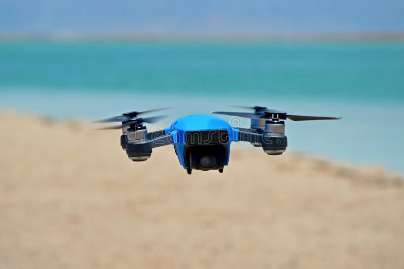 The Spark quadrocopter drone in rubber protection is hovering in the air against the background of the sea. A spark of new buzzing technology with a 15-minute royalty free stock photo
