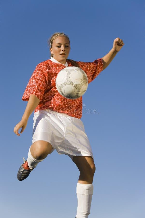 Sparka fotboll för fotbollspelare royaltyfri foto