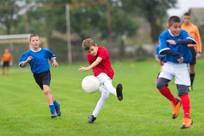 Sparka fotboll för pojke arkivbild