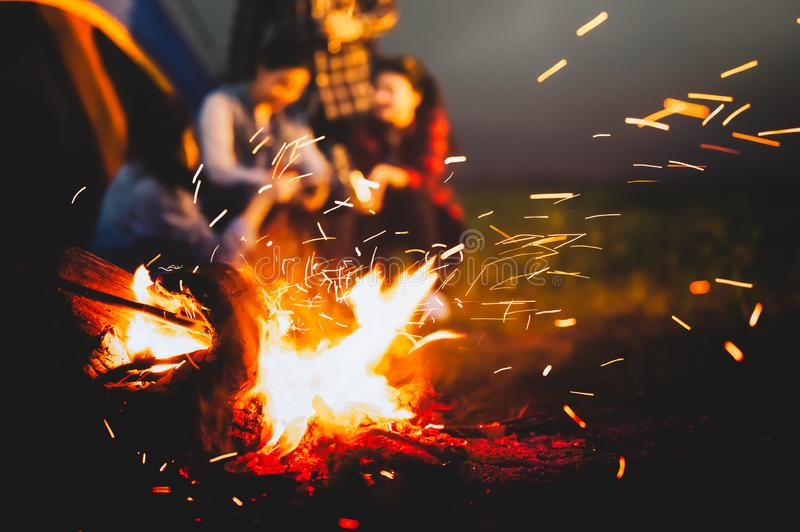 Sparking bonfire with tourist people sit around bright bonfire near camping tent in forest in summer night background. Group of royalty free stock photography