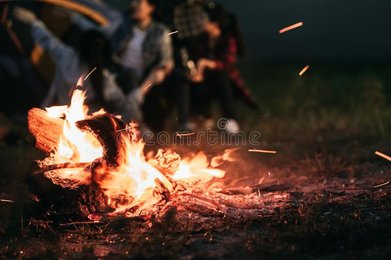 Sparking bonfire with tourist people sit around bright bonfire near camping tent in forest in summer night background. Group of stock photo