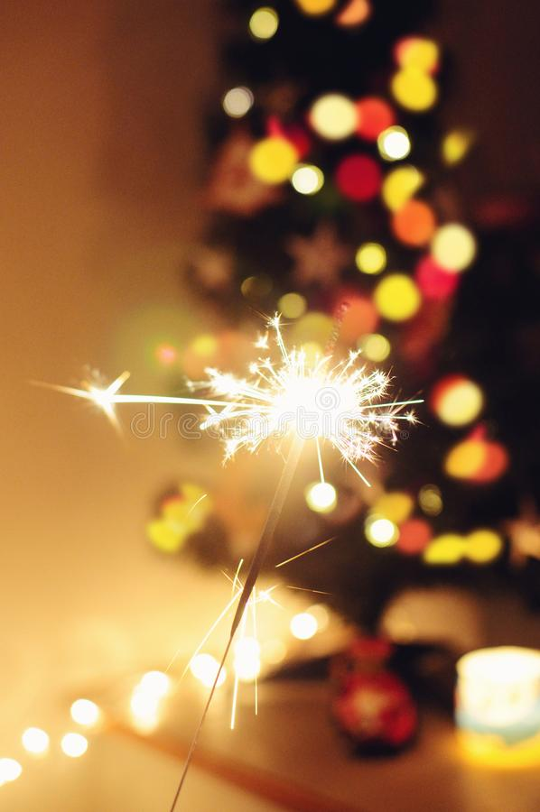 Sparkle stick. With lights and christmas tree on the background royalty free stock images