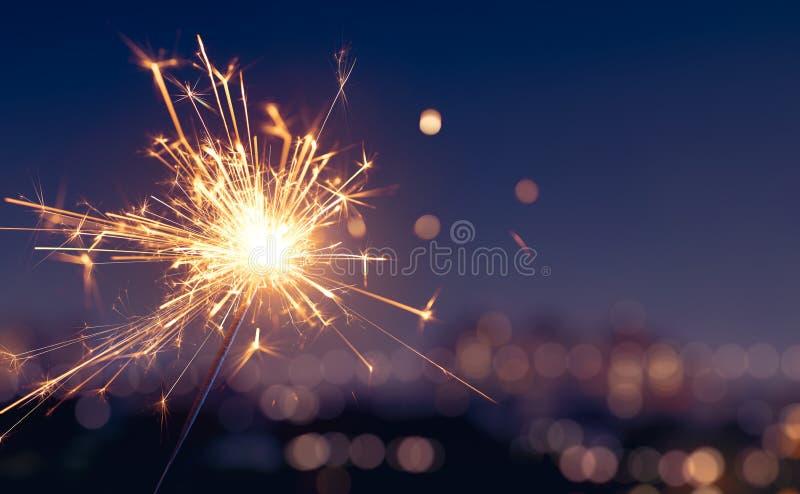 Sparkler με το θολωμένο ελαφρύ υπόβαθρο πόλεων στοκ φωτογραφία