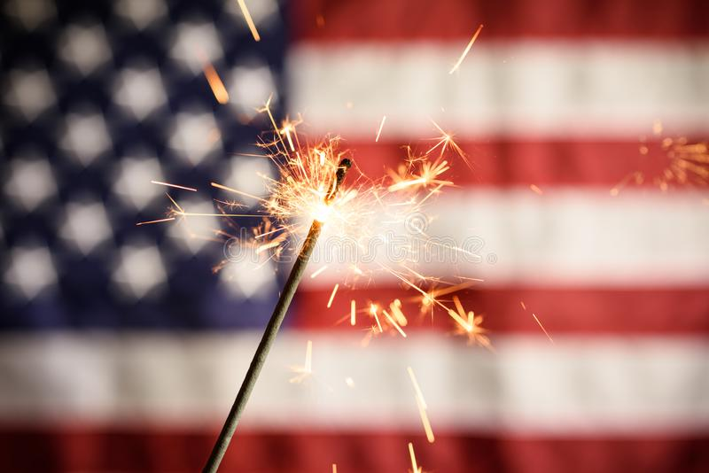 Sparkler Closeup With American Flag In Background. royalty free stock photos