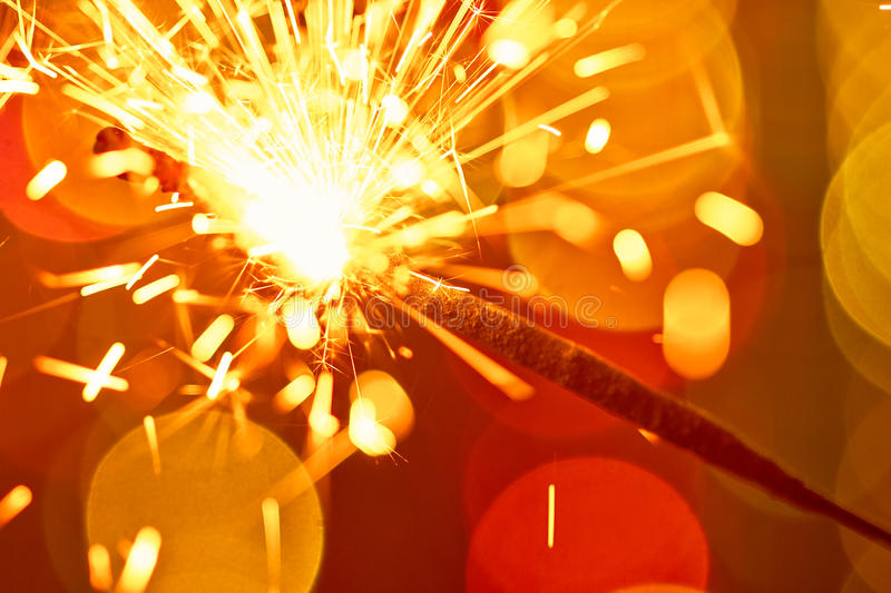 Sparkler on color bokeh background royalty free stock photography