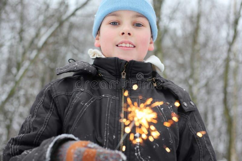 Sparkler del asimiento del niño pequeño en bosque imagen de archivo