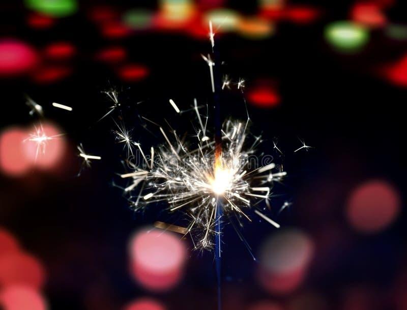 Sparkler fire on abstract glitter bokeh lights. stock photo