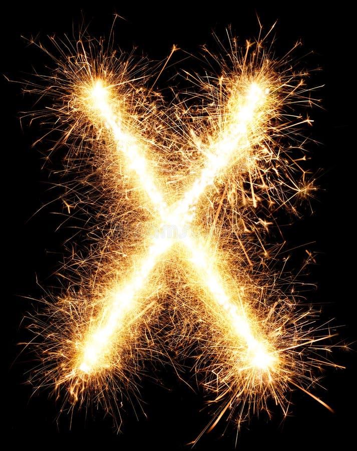 Sparkler firework light alphabet X on black. Background royalty free stock photo