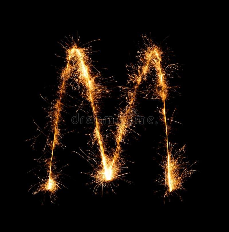Sparkler firework light alphabet M (Capital Letters) at night. Background royalty free stock images