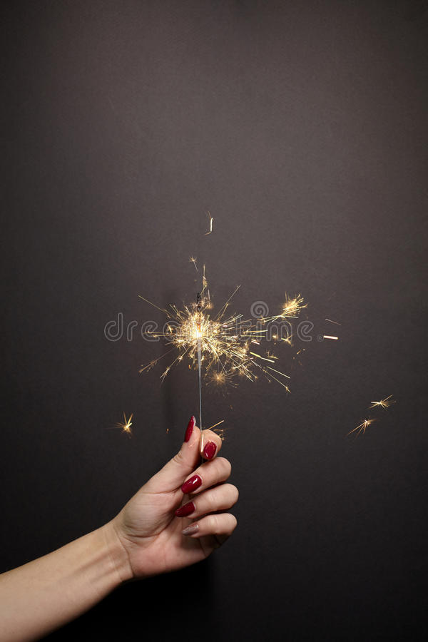 Free Sparkler In Woman Hand With Red Nail Polish Royalty Free Stock Images - 84405069