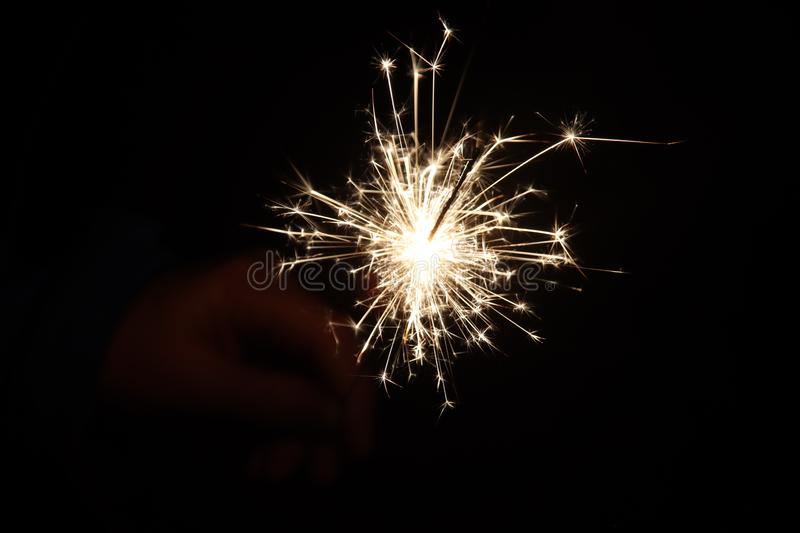 Sparkler with light and fire in hand of child during new years eve stock photography