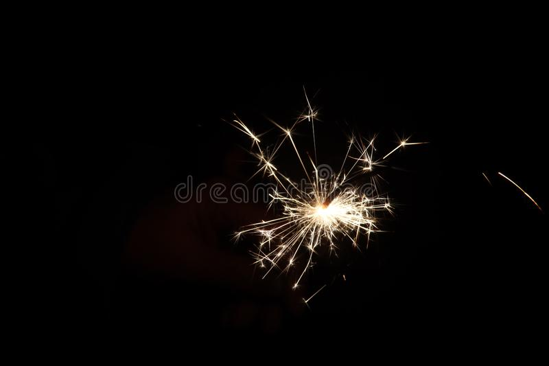 Sparkler with light and fire in hand of child during new years eve royalty free stock image