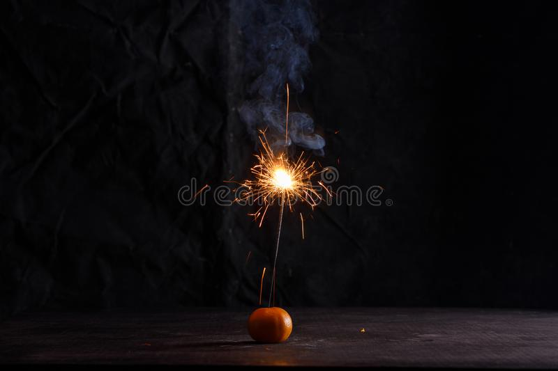 Sparkler in tangerine. Sparkler forming beautiful of star shape. Darkness is all around and effect of sparkling is amazing royalty free stock images