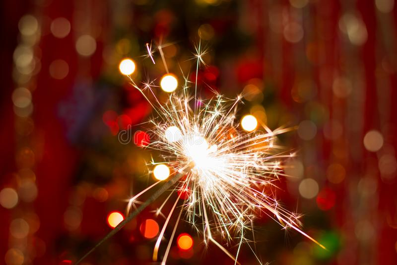 Sparklers κοντά στο χριστουγεννιάτικο δέντρο με ένα κόκκινο υπόβαθρο στοκ εικόνες με δικαίωμα ελεύθερης χρήσης