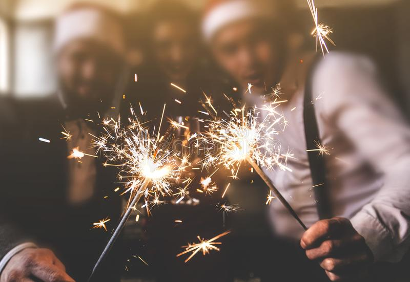 Sparklers in the foreground. Beautiful young people at a corporate party. New Year celebration. Club party with friends stock image