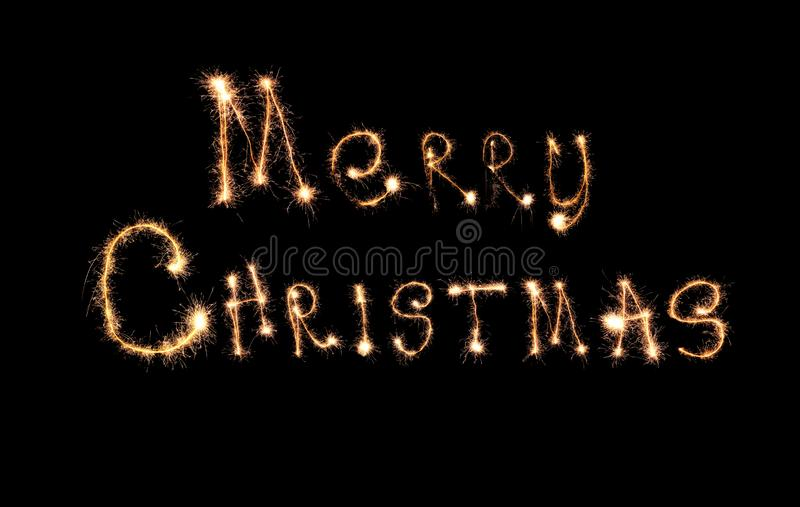 Sparklers forming text MERRY CHRISTMAS on black background royalty free stock image