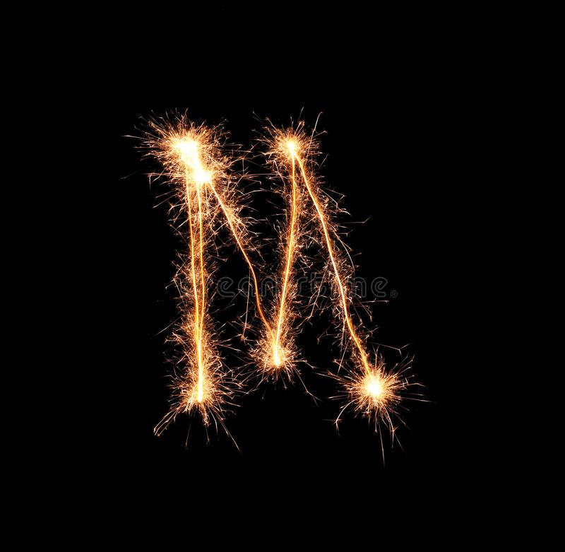 Sparklers tworzy list M na ciemnym tle zdjęcie stock