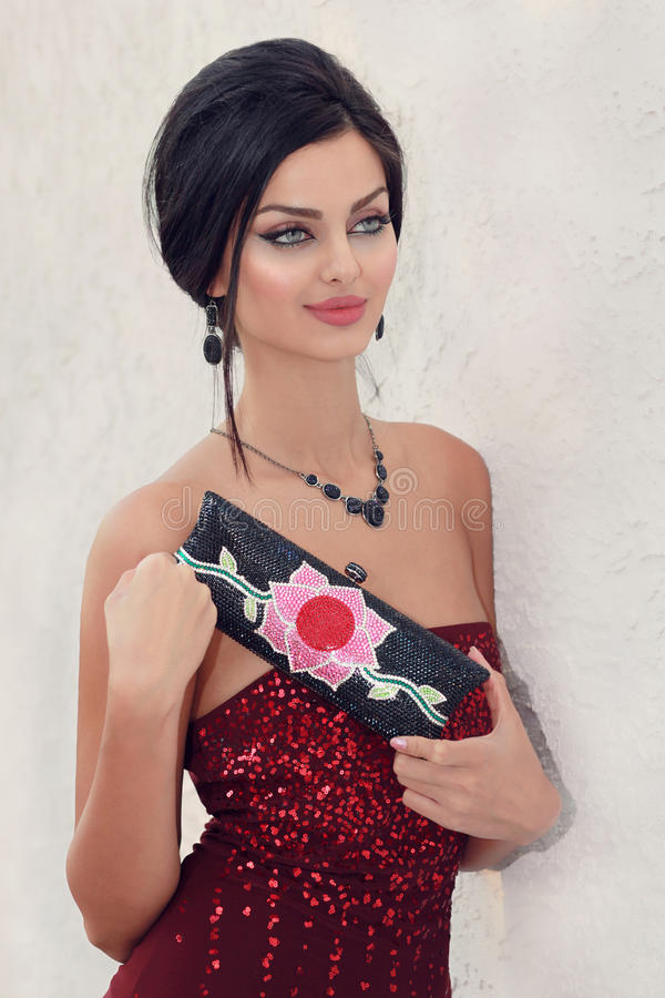 Sparkles and crystals. Young woman with a fashionable crystal handbag stock image